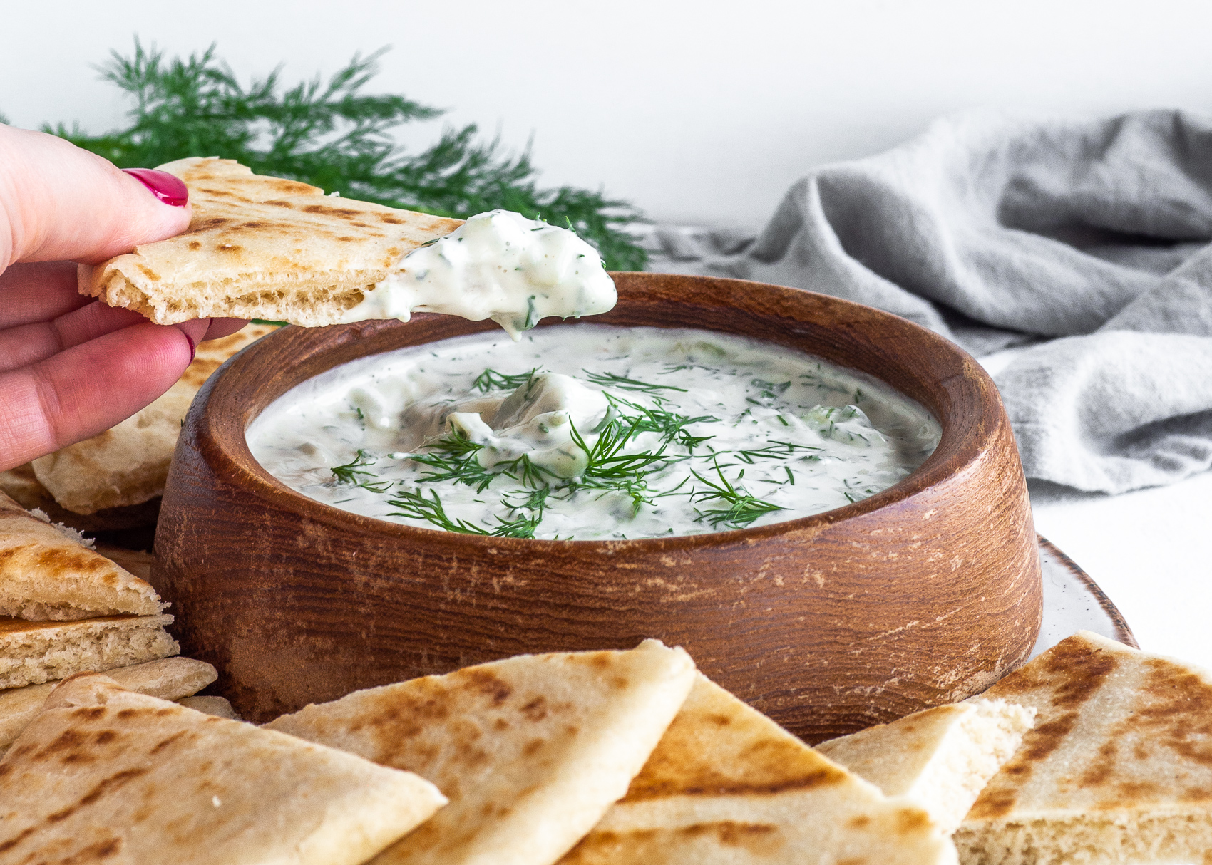 vegan tzatziki in wood bowl with hand dipping pita bread