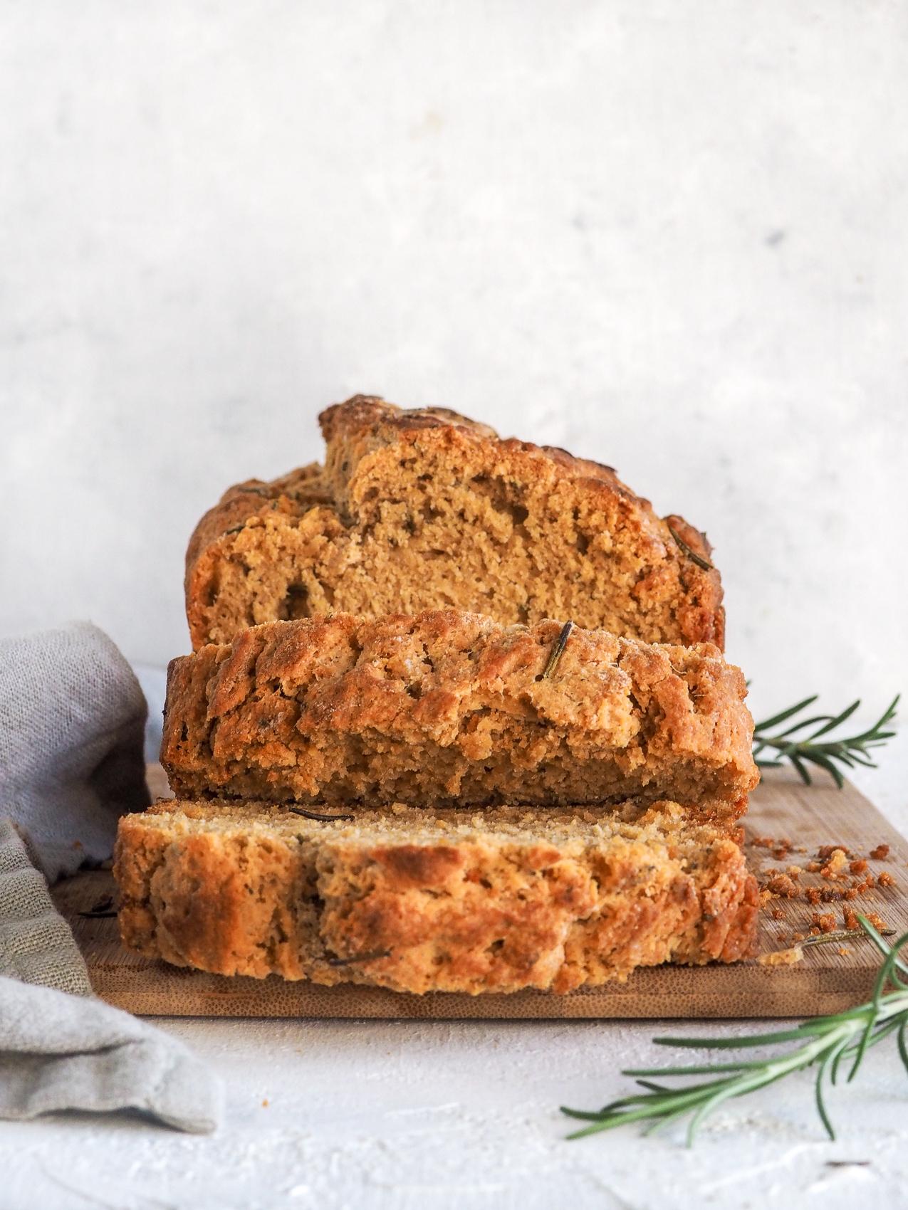 loaf of rosemary garlic beer bread on a wood cutting board