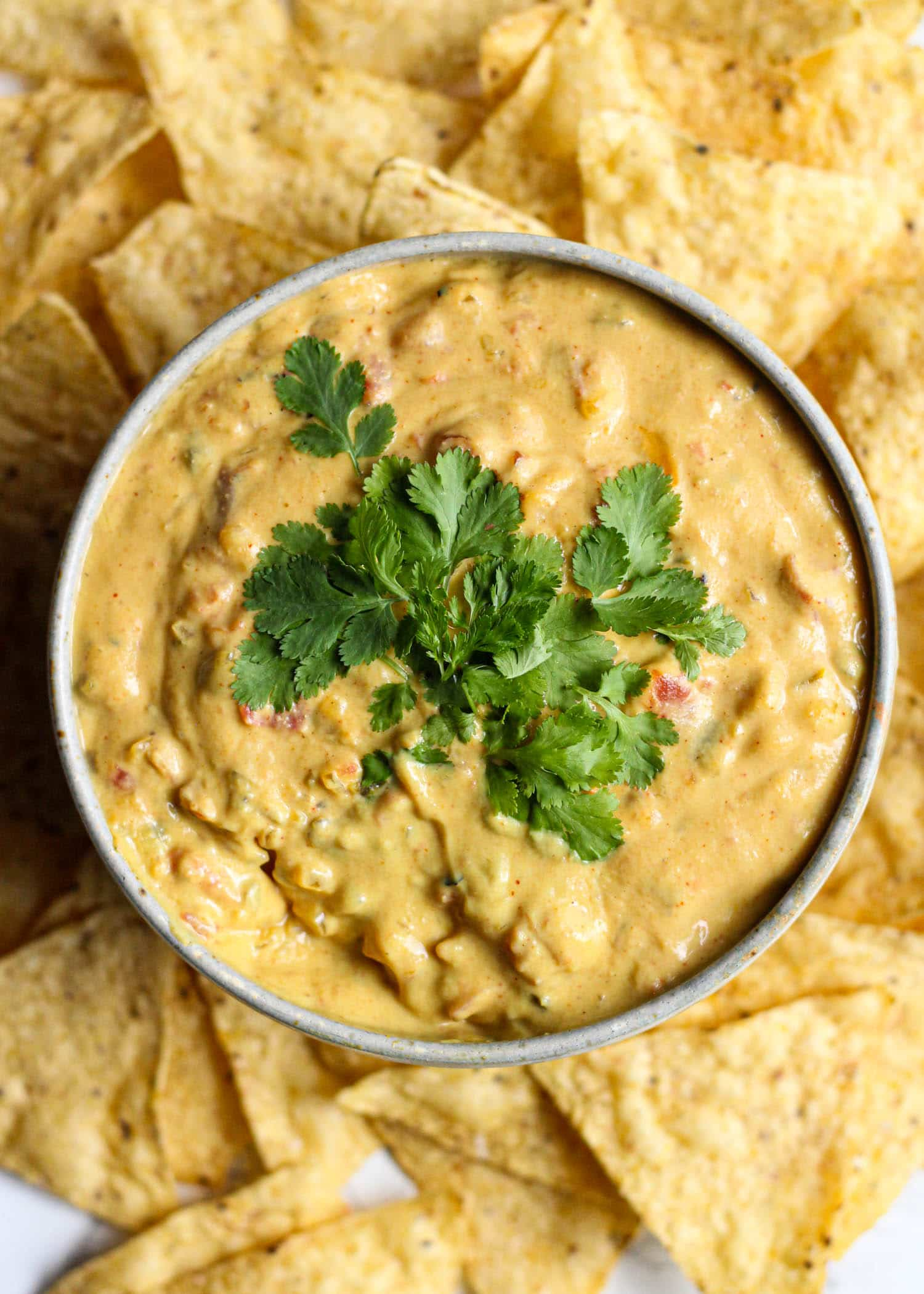 vegan nacho cheese in a bowl surrounded by tortilla chips